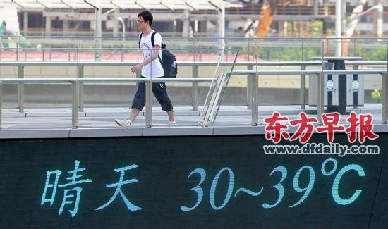 """昨日,一名行人走过陆家嘴连廊天桥,天桥的电子屏上显示着当日上海气温。早报记者张栋图src=""""http://y0.ifengimg.com/news_spider/dci_2013/07/4007fb0965d4401089c3457da82e32c6.jpg"""""""