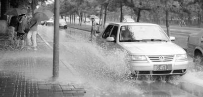 """一辆银灰色轿车快速驶过,溅起水花淋了路人一身 网友""""弓长大牙""""供图"""