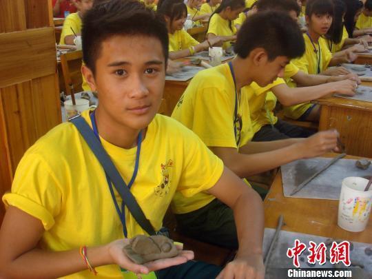 原标题:传统陶艺课让54名海外华裔青少年寻到中国根  7月14日,来自老挝沙湾拿吉崇德学校的华裔学生苏梦狄展示他刚刚做好的一条大嘴鱼。7月14日,来自老挝、匈牙利、美国、阿联酋的54名海外华裔青少年,在桂林市少年宫学习中国传统文化陶艺课。 欧惠兰 摄  7月14日,来自老挝、匈牙利、美国、阿联酋的54名海外华裔青少年,在桂林市少年宫学习中国传统文化陶艺课。 欧惠兰 摄 中新网桂林7月14日电 题:传统陶艺课让54名海外华裔青少年寻到中国根 作者:欧惠兰 7月14日,来自老挝、匈牙利、美国、阿联酋等国