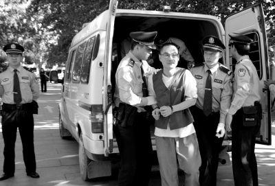 """韩磊被带出警车准备进入法庭。京华时报通讯员李佳摄登录手机应用平台,免费下载并使用""""云拍"""",拍摄图片观看视频。"""