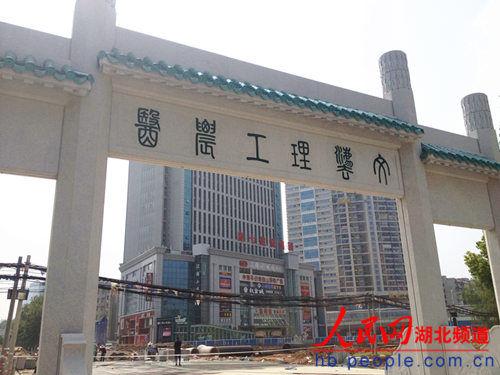 """武大新牌坊反面深绿色的""""文法理工农医""""六字,在蓝天白云下显得熠熠生辉。"""