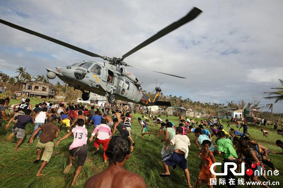 当地时间2013年11月16日,菲律宾萨尔塞多,美国海鹰号直升机向地面投送救援物资引发灾民争抢。图片来源:FRANCIS R. MALASIG/CFP