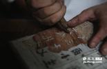 """木刻雕版印刷中最为重要的技艺就是刻版,刻工按字迹墨线精雕细刻,先按笔划划刻,后将空白部分剔除,使墨迹形成约1毫米凸起的阳文反字。开刻之前先在字迹周围划刻一刀,放松木面,称""""发刀"""",实刻则以右手握刀,左手拇指抵助,先刻直线,再横放书板,逐一雕刻点、勾、撇、捺,完成全字。"""