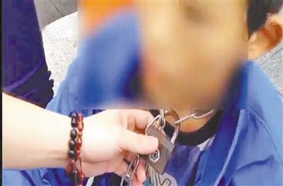 幼强脖子上被拴着铁锁。