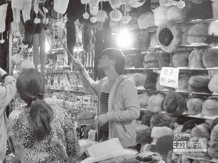 在城市里摆帽子幼铺的大陆人。来源:台湾《旺报》