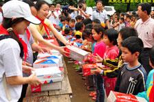 志愿者给孩子们发放文体用品